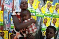 A woman holds her sick child next to banners for the upcoming presidential elections in Petion Ville, Port-au-Prince