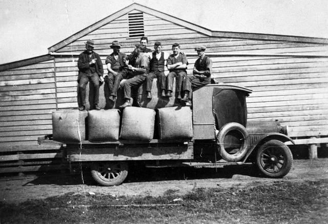 SHEARERS SITTING ON WOOL BALES ON A TRUCK